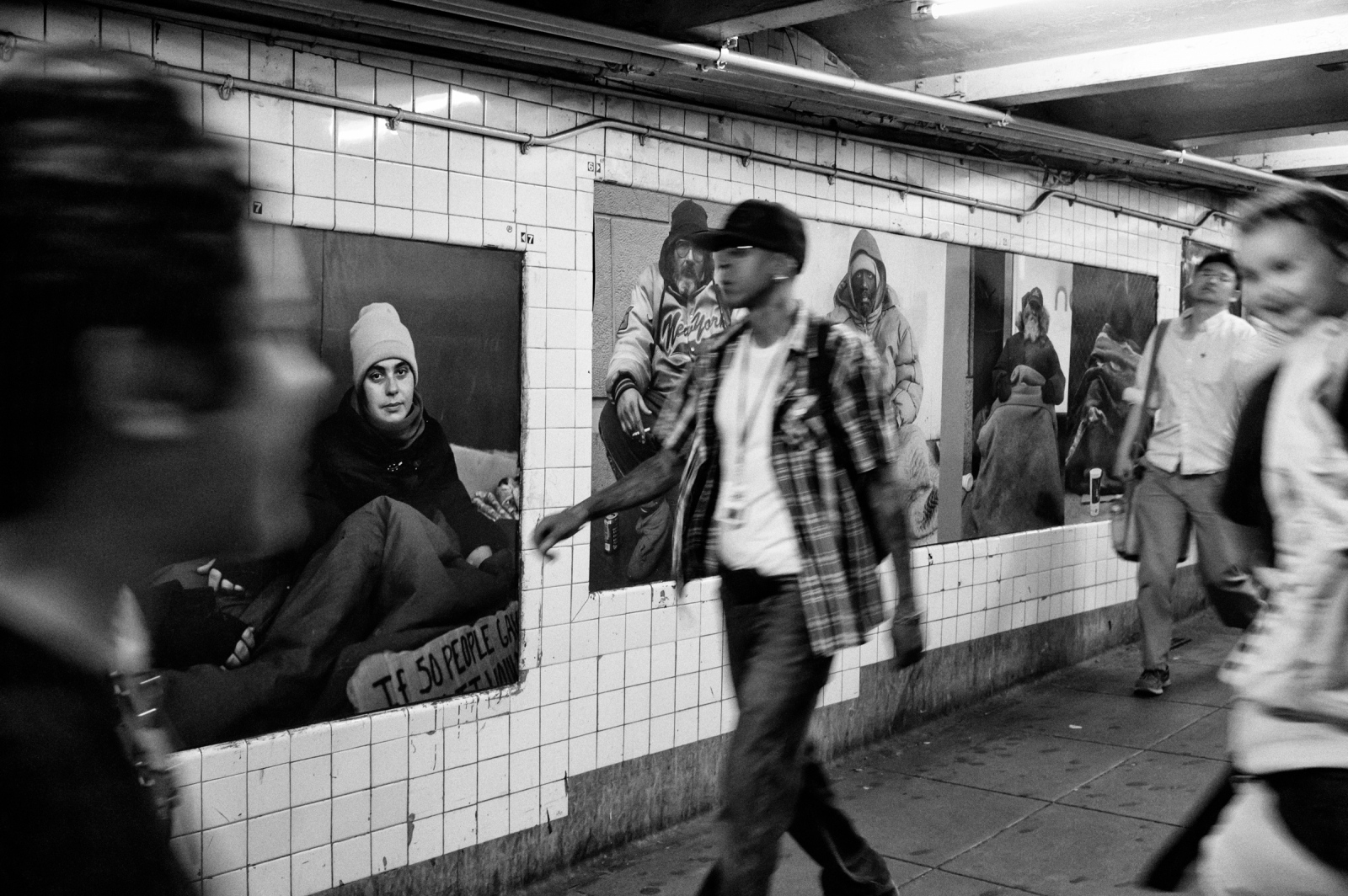 People walk through a pathway and photo campaign for homeless in NY by Andres Serrano are seen on the wall in W 4 St subway station on Jun. 16, 2014 in Manhattan, New York.